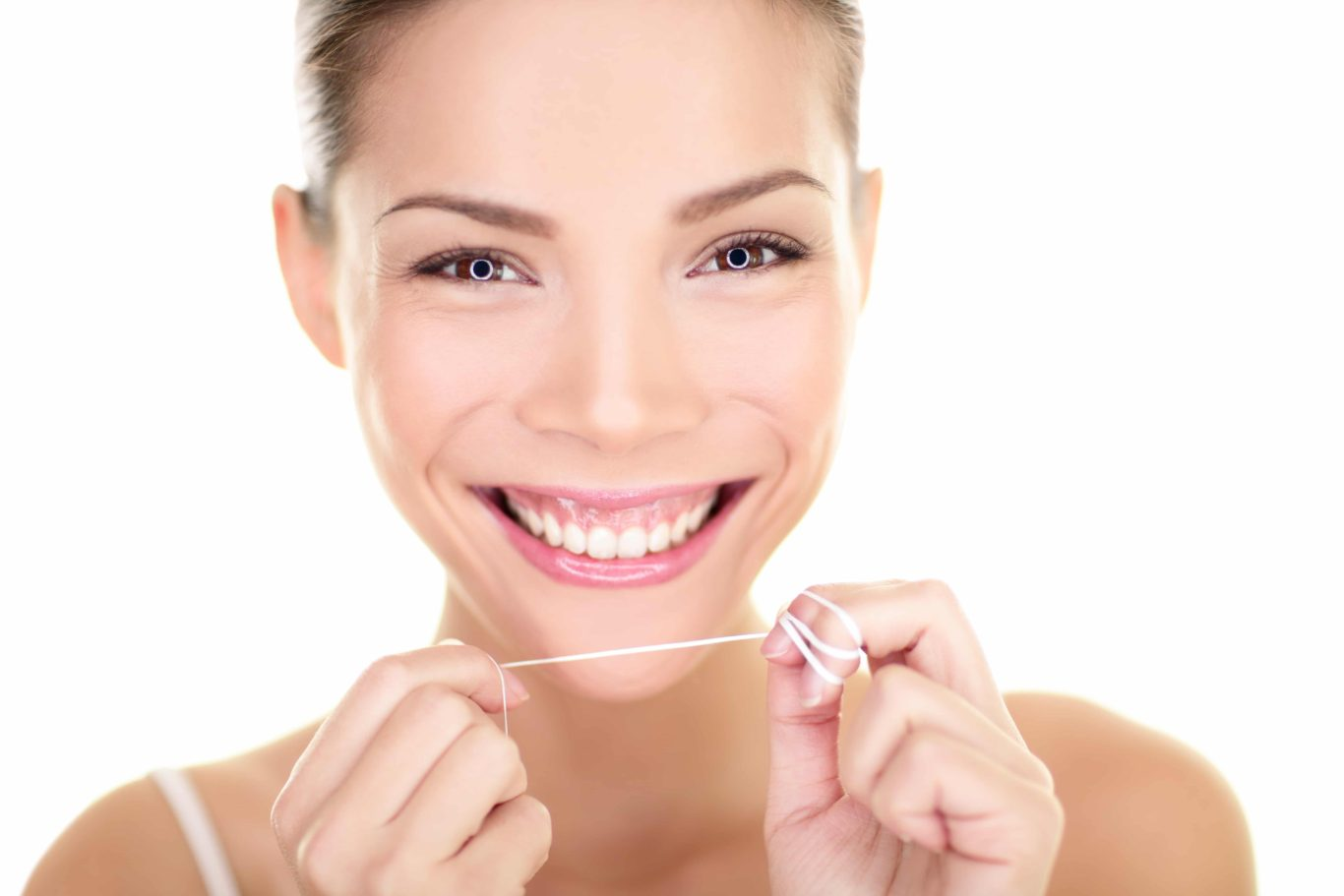 Woman Flossing Teeth While Smiling