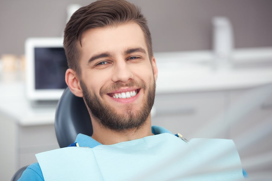 Smiling Man in a Chair Waiting for a Dental Checkup